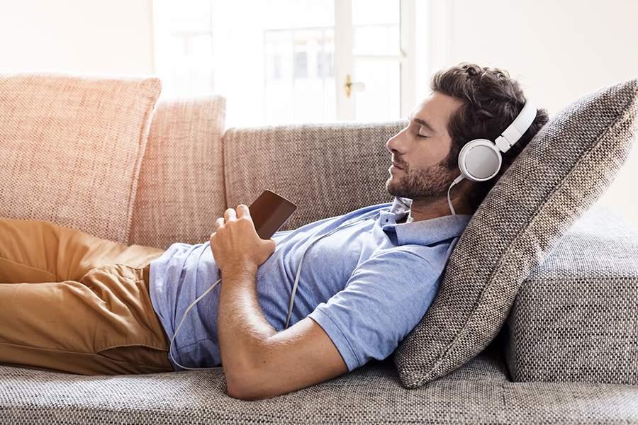 Hombre en el sofá con audifonos