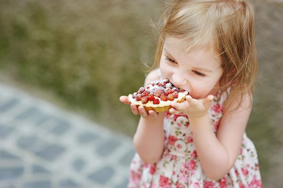 Niña comiendo en un picnic