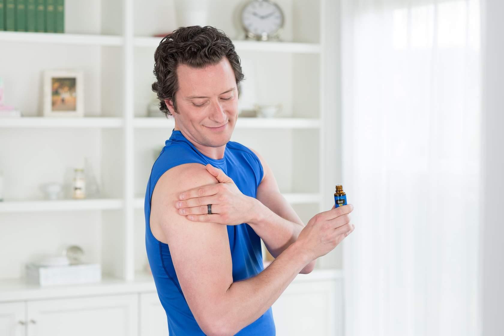man using essential oils on shoulder