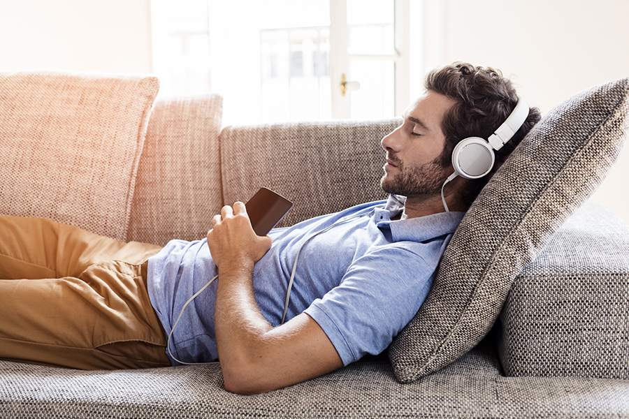 man on couch with headphones on